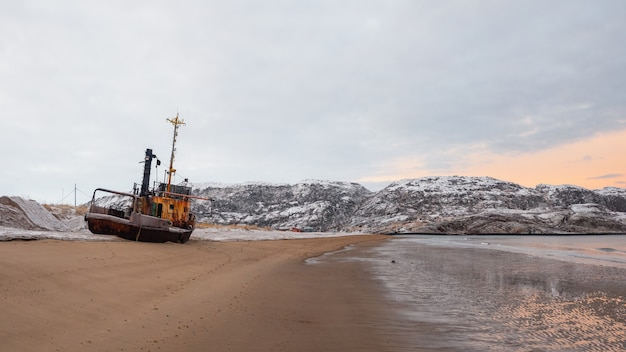 Stara zardzewiała łódź rybacka porzucona przez burzę na brzegu. widok panoramiczny. półwysep kolski, teriberka, rosja.