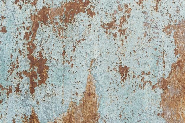 Stara zardzewiała powierzchnia z pękniętą niebieską farbą