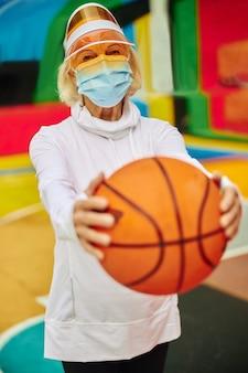 Stara, zdrowa i wesoła dama na kolorowym kwadracie na zewnątrz w masce i trzymająca piłkę do koszykówki