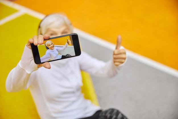 Stara, zdrowa i wesoła dama na kolorowym kwadracie na zewnątrz w słuchawkach i trzymająca smartfona
