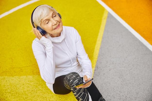 Stara, zdrowa i wesoła pani na kolorowym placu na zewnątrz w słuchawkach i słuchając muzyki