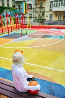 Stara, zdrowa i wesoła pani z piłką do koszykówki na kolorowym kwadracie na zewnątrz