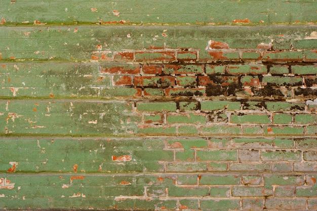 Stara zieleń wietrzał podławego ściana z cegieł z uszkadzającą tynku tła teksturą
