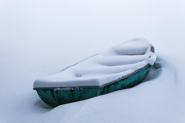 Stara zielona łódź w zamarzniętym jeziorze.