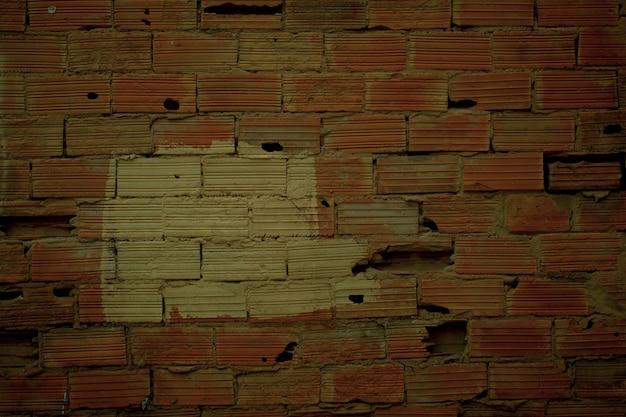 Stara zniszczona tekstura ściany z czerwonymi prążkowanymi cegłami, których brakuje lub są uszkodzone, oraz pomalowana na biało łata w środku