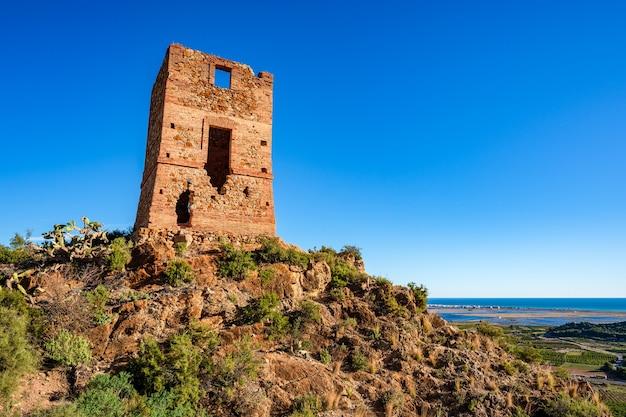 """Stara zrujnowana wieża strażnicza zwana """"l'ageleta"""" na szczycie wzgórza."""