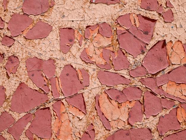 Stara, zwietrzała, łuszcząca się farba jest czerwona na ścianie. zbliżenie, tło, tekstura