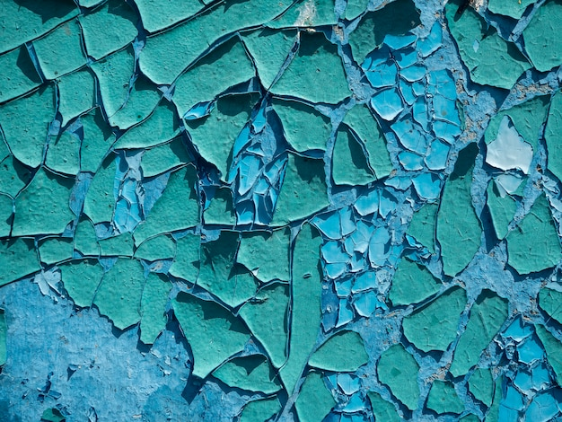 Stara, zwietrzała, łuszcząca się farba jest niebieska na ścianie. zbliżenie, tło, tekstura