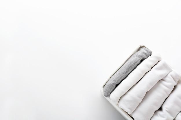 Starannie poskładane biało-szare ubrania w pojemniku na szafę lub wycieczkę na biało. porządek w szafie.