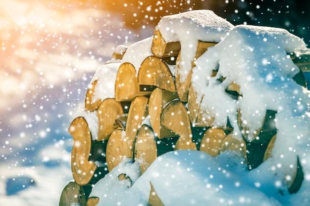 Starannie ułożony stos posiekanego suchego pnia drewna pokrytego śniegiem