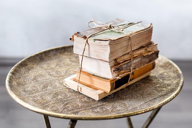 Stare 100-letnie książki na temat antycznego stołu zbliżenie, historia, wiedza, nostalgia, koncepcja starości.