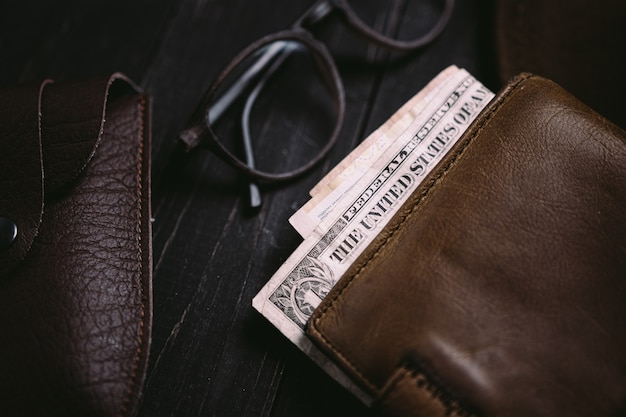 Stare banknoty w portfelu vintage. płaskie ułożenie drewnianego biurka podróżnego