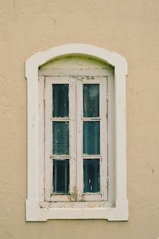Stare białe okno na jasnoróżowej ścianie