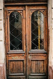 Stare brązowe drewniane drzwi domu z oknami, budynek.