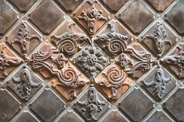 Stare brązowe płytki z terakoty zdobione motywami kwiatowymi
