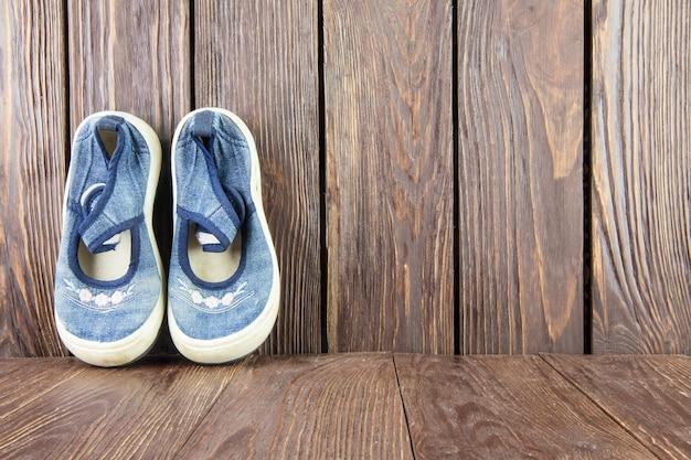 Stare buty dla dzieci na tle drewna