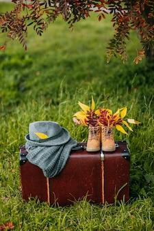 Stare buty, filcowy kapelusz i dzianinowy szalik na brązowej walizce vintage w jesiennym lesie