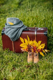 Stare buty, filcowy kapelusz i dzianinowy szalik z brązową walizką vintage w jesiennym lesie