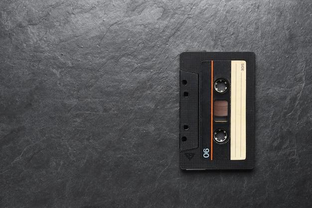 Stare czarne kasety kompaktowe z taśmą audio na czarnym łupku