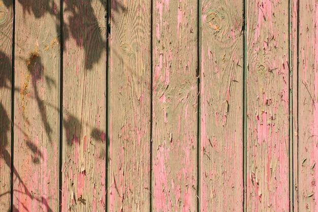 Stare drewniane deski tło. łuszcząca się, wyblakła różowa farba na starych deskach z cieniem gałęzi drzew
