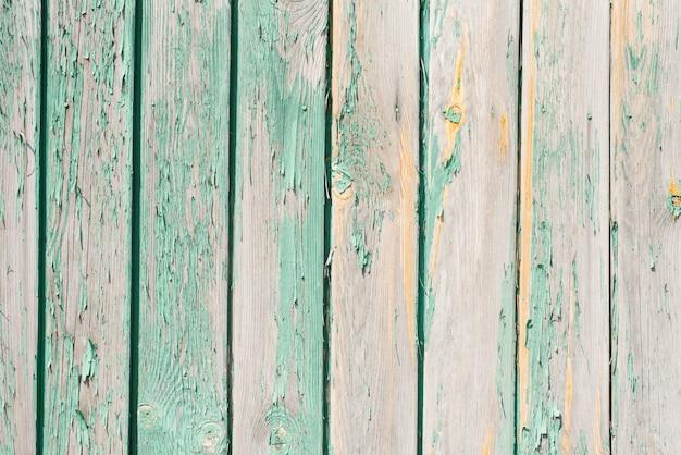 Stare drewniane deski tło. łuszcząca się, wyblakła turkusowa farba na starych deskach. kopiowanie miejsca