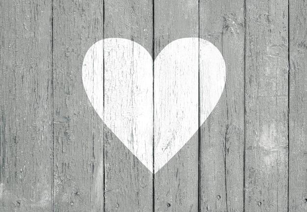 Stare drewniane deski tło z pękniętą szarą farbą i kształtem białego serca. koncepcja walentynki i miłość