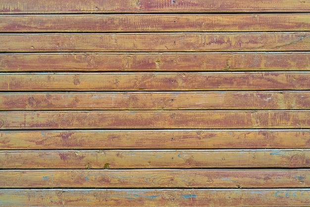 Stare drewniane deski w stylu vintage pokryte łuszczącą się brązową farbą. tekstura drewna.