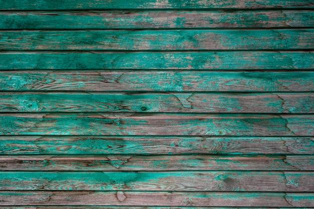 Stare drewniane deski z łuszczącą się zieloną farbą. zielona farba zejdzie z drewnianych desek. zielona farba ze starą drewnianą powierzchnią