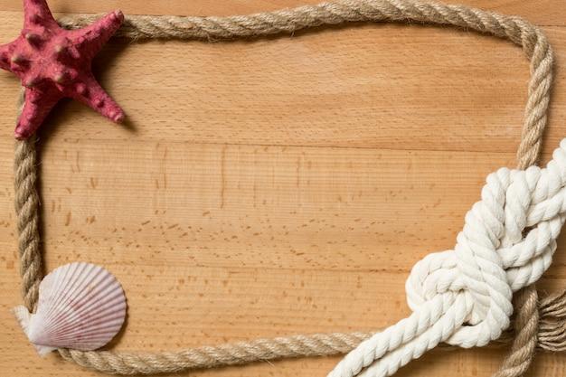 Stare drewniane deski z ramą ze sznurka ozdobione węzłem morskim i muszlami