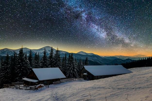 Stare drewniane domy w głębokim śniegu na górskiej dolinie.
