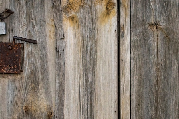 Stare drewniane drzwi i zardzewiała żelazna kołatka