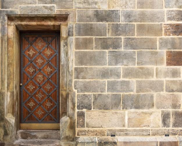 Stare drewniane drzwi na scenie kamiennego muru