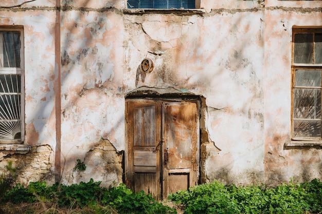 Stare drewniane drzwi na zwietrzałej i zapadającej się ścianie.