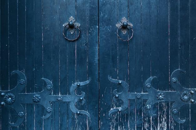 Stare drewniane drzwi z kutymi zawiasami, drewniana tekstura starych drzwi z elementami kującymi