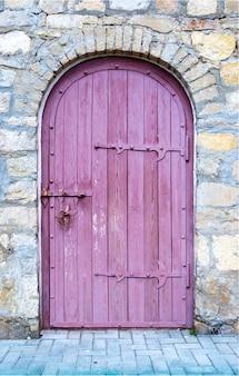 Stare drewniane drzwi z zamkiem w starym kamiennym murem.