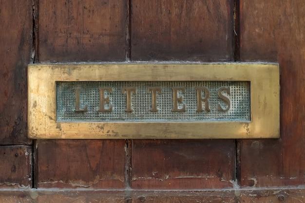 Stare drewniane drzwi ze skrzynką pocztową z bliska