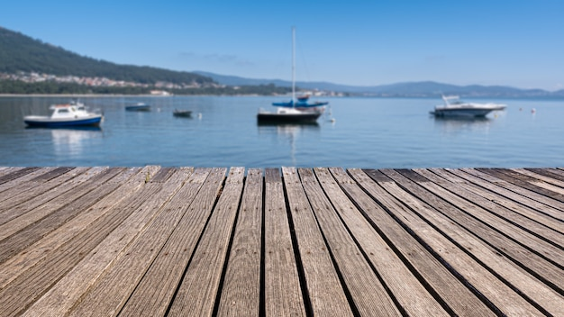 Stare drewniane kładki nad brzegiem morza z niewyraźne tło i łodzie