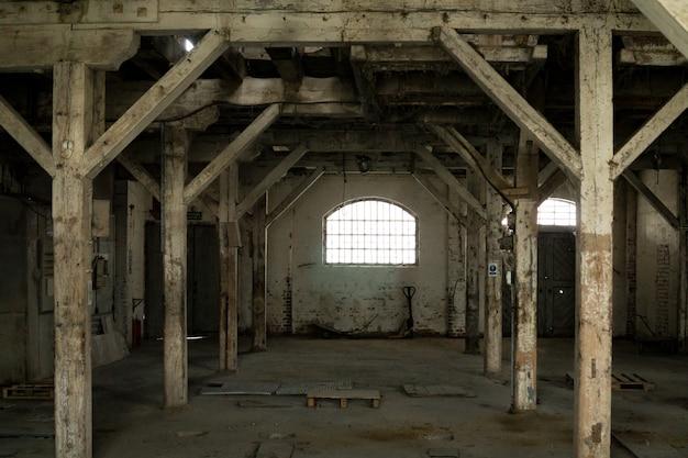 Stare drewniane kolumny. stary opuszczony magazyn, oświetlony światłem z okna.