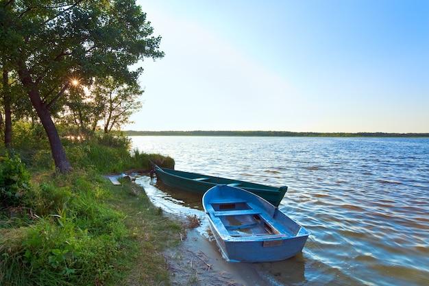 Stare drewniane łodzie rybackie w pobliżu letniego brzegu jeziora (świtaź, ukraina)