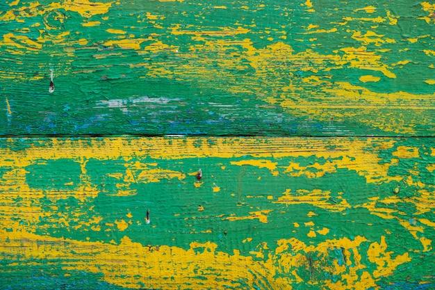 Stare drewniane malowane rustykalne ściany z żółto-zielony płatkowaty barwnik. z bliska wyblakłe deski drewniane. łuszczenie farby na pokładzie. uszkodzona szorstka drewniana tekstura. niedoskonała powierzchnia drewna. tło z wyblakły lakier.