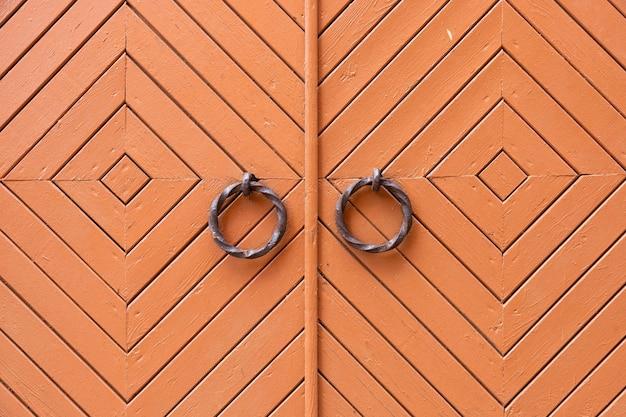 Stare, drewniane, metalowe drzwi, zamykane na zamek.