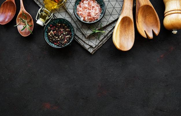 Stare drewniane naczynia kuchenne i przyprawy jako obramowanie na czarnym tle