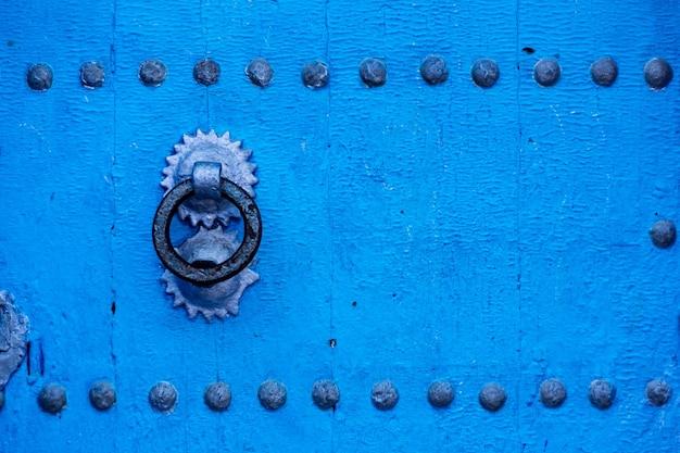 Stare drewniane niebieskie drzwi w słynnej niebieskiej wiosce chefchaouen w maroku