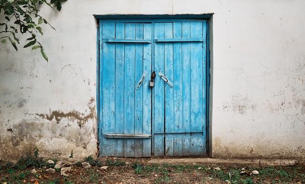 Stare drewniane niebieskie drzwi w starej ścianie z kruszącym się tynkiem