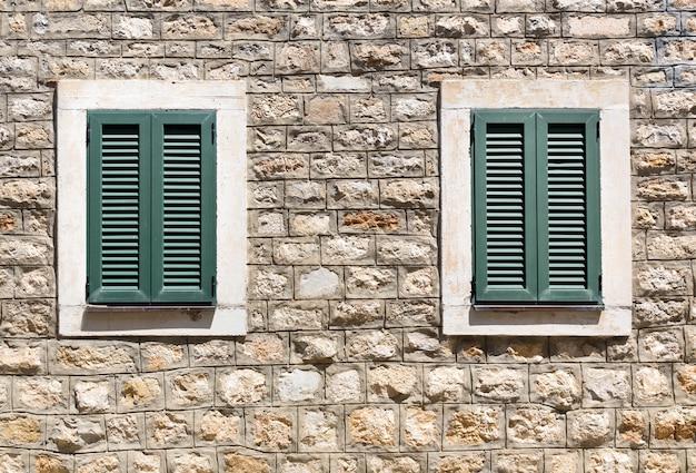 Stare drewniane okna w kamiennej ścianie
