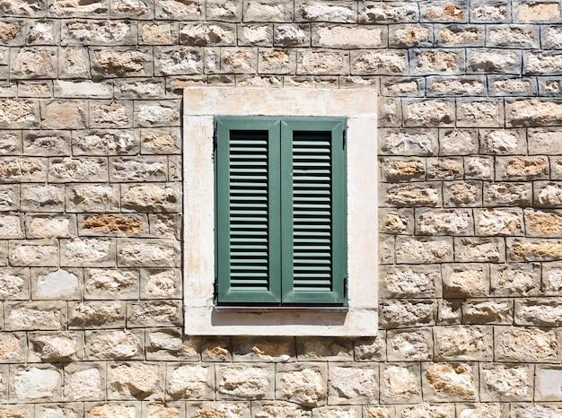Stare drewniane okno w kamiennej ścianie