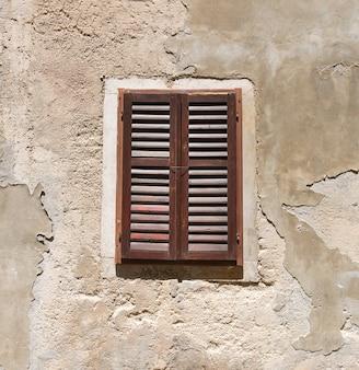 Stare drewniane okno w popękanej ścianie