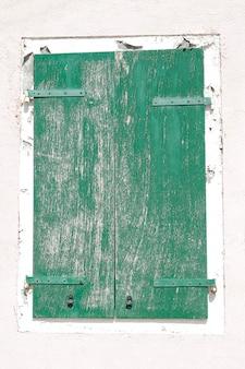 Stare drewniane okno z zielonymi okiennicami na pomalowanej na biało ścianie, na wyspie burano, wenecja, włochy