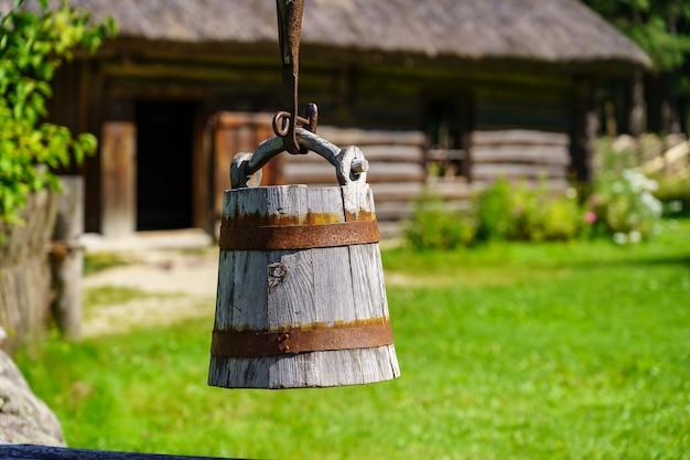 Stare drewniane wiadro do czerpania wody ze studni w polu.
