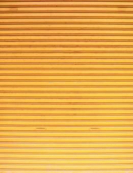 Stare drzwi metalowe rolety ze stopu cynku w wieku vintage, teksturowane w kolorze żółtym
